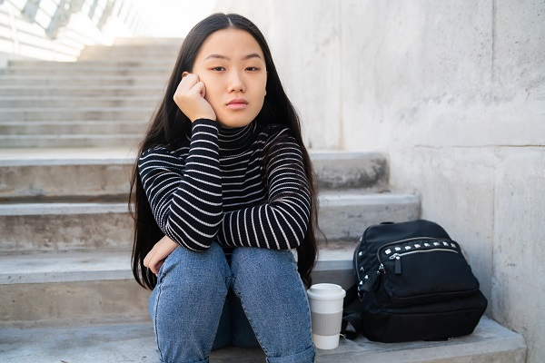 Asian woman sitting on concrete stairs.